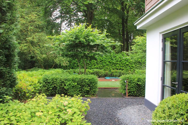 Door beplanting met oplopende hoogte ontstaat een visuele verbinding met de bomen buiten de tuin.