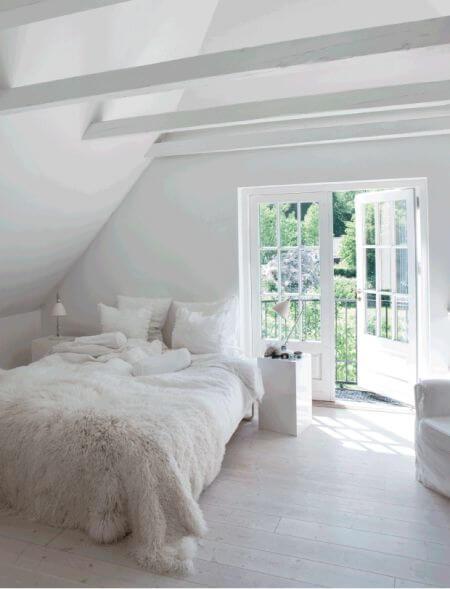 grote witte slaapkamer met openslaande deur