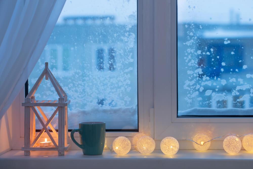 Lichtsnoer van kerstlampjes in de vensterbank